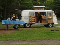 Author enjoying a hot coffee and a good book at a KOA campground in Northern Ontario.  Note the Westy\'s pop-up roof, 180-degree opening side doors, \